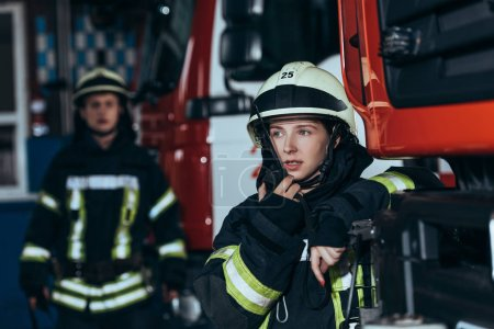 Photo for Selective focus of female firefighter talking on portable radio set with colleague behind at fire department - Royalty Free Image