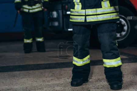 partial view of firefighters in protective fireproof uniform standing at fire station