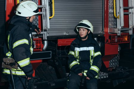 firefighters in fireproof uniform and helmets having conversation at fire station