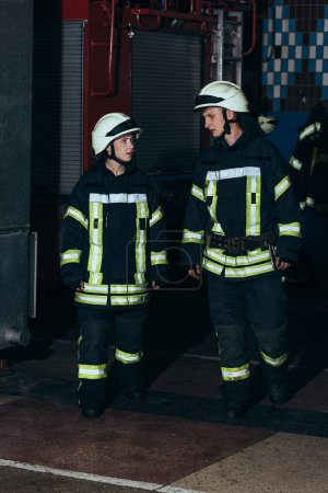 firefighters in protective uniform and helmets at fire department
