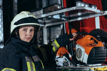 portrait of female firefighter standing at equipment in truck at fire department