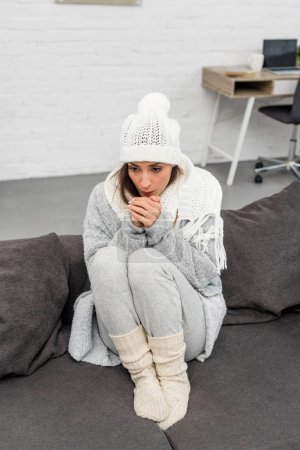 high angle view of freezed young woman in warm clothes sitting on couch at home and blowing at hands
