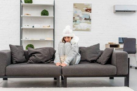 zamarznięty młoda kobieta w ciepłe ubrania, siedział na kanapie w salonie