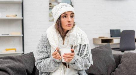 Photo pour Jeune femme congelée dans des vêtements chauds tenant tasse de thé chaud tout en étant assis sur le canapé à la maison - image libre de droit