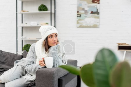 Photo for Thoughtful young woman in warm clothes holding cup of hot tea and looking away while sitting on couch - Royalty Free Image