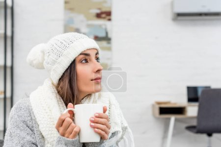 thoughtful young woman in warm clothes holding cup of hot tea at home and looking away