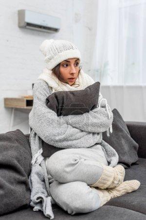 Photo pour Femme choquée figée dans des vêtements chauds, assis sur le canapé et étreindre le coussin à la maison - image libre de droit
