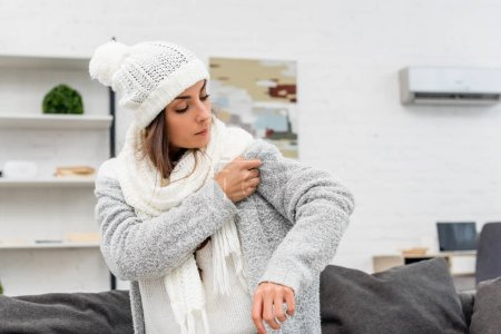 freezed young woman putting on warm clothes with air condition hanging on background