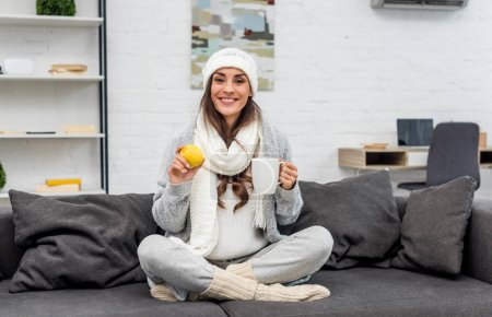 happy young woman in warm clothes holding lemon and cup of tea at home
