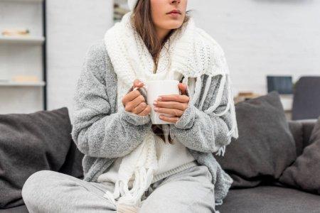 Foto de Recortar el tiro de enferma joven en ropa de abrigo con taza de bebida caliente mientras está sentado en el sofá en casa - Imagen libre de derechos
