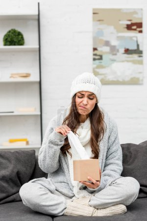 sick young woman in warm clothes taking paper napkin from box while sitting on couch