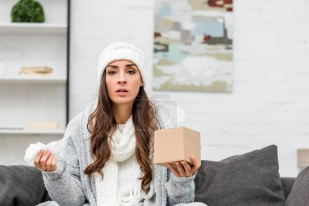 sick young woman in warm clothes sitting on couch at home and holding box of paper napkins