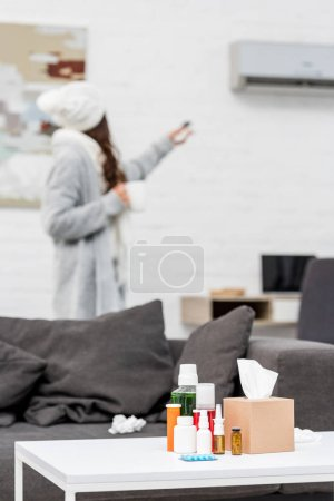 sick woman in warm clothes pointing at air conditioner with remote with various medicines standing on table on foreground