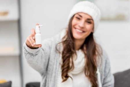 sick young woman in warm clothes showing nose spray at camera