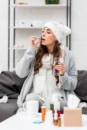 sick young woman in warm clothes taking pill on couch at home