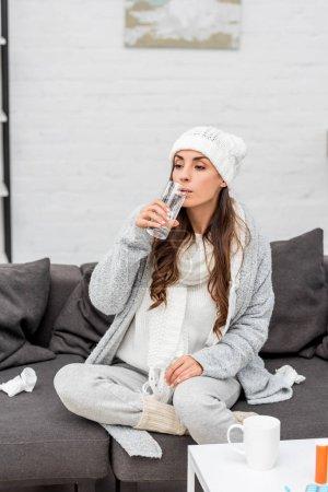 Photo pour Jeune femme malade en vêtements chauds boire de l'eau sur le canapé à la maison - image libre de droit