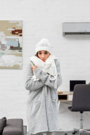 freezing young woman in warm clothes with air conditioner on background