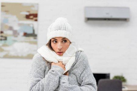 Photo pour Portrait en gros plan de la jeune femme gelée en vêtements chauds avec climatiseur sur fond - image libre de droit