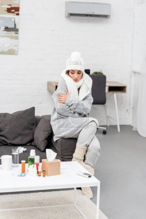 sick young woman in warm clothes sitting on couch and looking at medicines on table