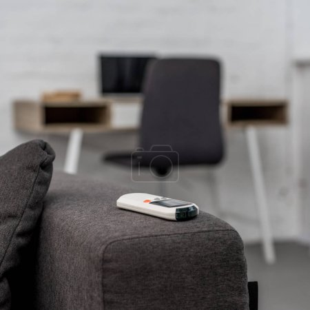 close-up shot of air conditioner remote control lying on sofa with workplace on background