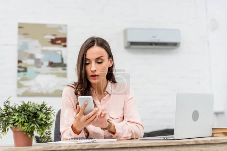 attractive young businesswoman using smartphone while working at office