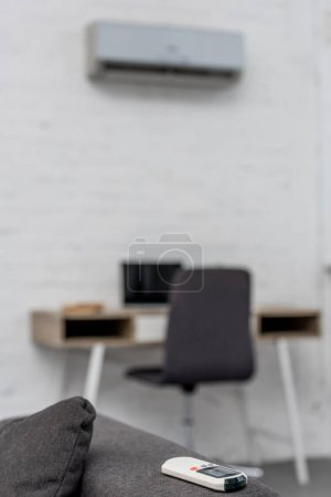 close-up shot of air conditioner remote control lying on couch with workplace on background