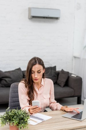 beautiful young businesswoman using smartphone while working at office