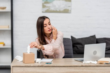 sick young businesswoman talking by phone and taking paper napkin out of box at workplace