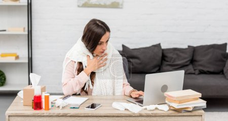 sick young businesswoman in scarf working with laptop at workplace