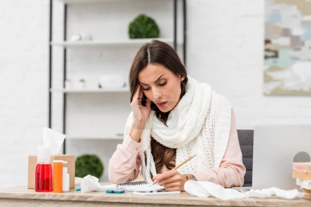 Photo for Sick young businesswoman trying to work while suffering from headache at workplace - Royalty Free Image