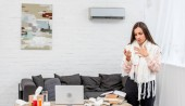 sick young businesswoman standing near workplace in office