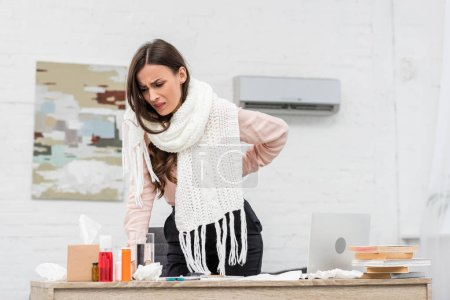 suffering sick businesswoman leaning on workplace with medicines