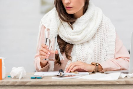 cropped shot of sick young woman in scarf holding glass of water at workplace