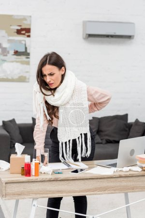 suffering sick young businesswoman leaning on workplace with medicines