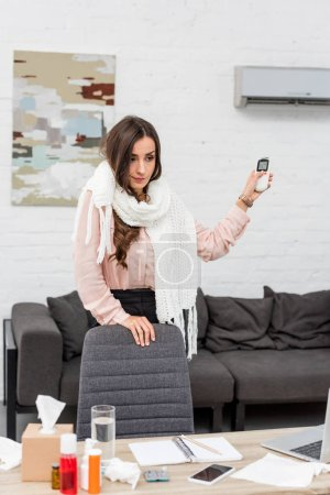 sick young woman at workplace pointing at air conditioner with remote control