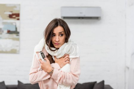 freezed young woman in scarf holding remote control with air conditioner on background