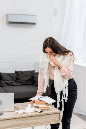 sick young woman reading and sneezing at office