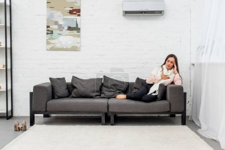 ill young woman lying on couch under air condition at home