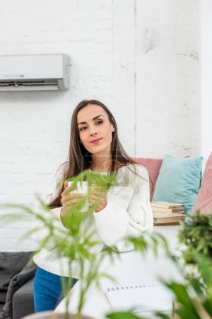beautiful young woman holding cup of coffee while leaning on windowsill