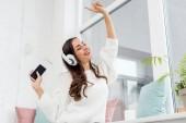 """Постер, картина, фотообои """"вид снизу прослушивания музыки Счастливая молодая женщина с смартфонов и беспроводные наушники на дому"""""""