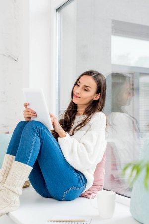 Foto de Mujer joven feliz con tableta en el alféizar de la ventana con cojines en casa - Imagen libre de derechos