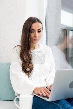 Foto de Hermosa joven freelance con taza de café, trabajando con el portátil en el alféizar de la ventana en casa - Imagen libre de derechos