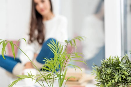 Photo for Selective focus of beautiful young woman sitting on windowsill at home with houseplants on foreground - Royalty Free Image