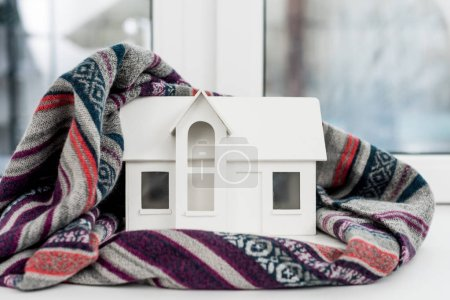 close-up shot of miniature house model with plaid on windowsill