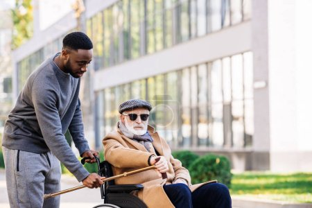 Photo for African american man giving walking stick to senior disabled man in wheelchair on street - Royalty Free Image