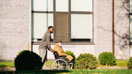 Photo for Senior disabled man in wheelchair and african american man having morning walk on street - Royalty Free Image