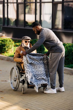 Photo for African american nurse covering senior disabled man in wheelchair with plaid on street - Royalty Free Image