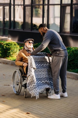 Photo for Young african american cuidador covering senior disabled man in wheelchair with plaid on street - Royalty Free Image