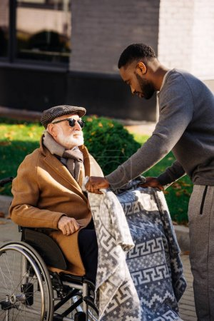 Photo for African american man covering senior disabled man in wheelchair with plaid on street - Royalty Free Image