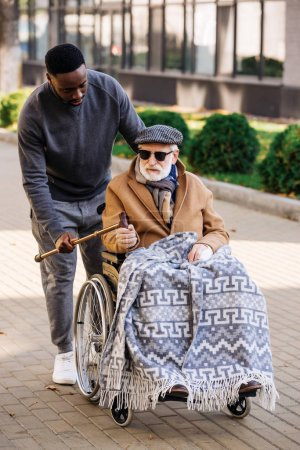 african american man giving walking stick to senior disabled man in wheelchair on street